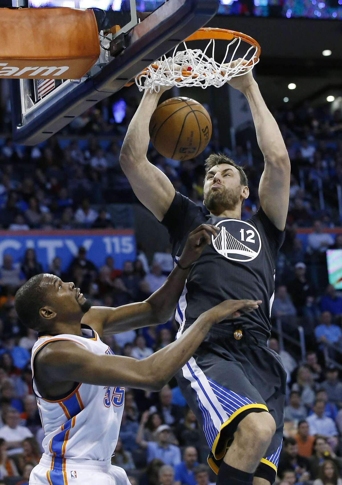 Golden State Warriors center Andrew Bogut (12) dunks in front of Oklahoma City Thunder forward Kevin Durant (35) during the second quarter of an NBA basketball game in Oklahoma City, Saturday, Feb. 27, 2016.