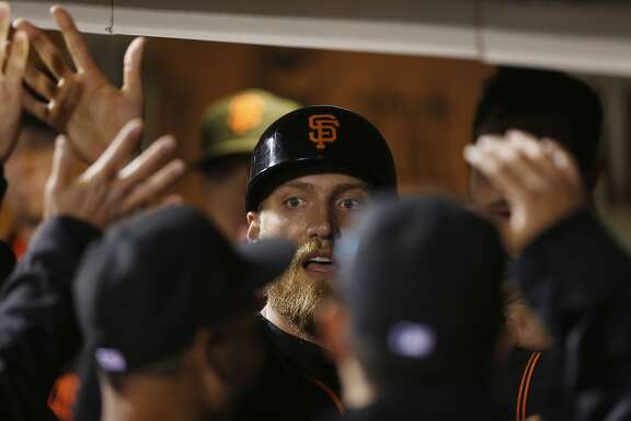 San Francisco Giants' Hunter Pence is congratulated after scoring a run on a single hit by Brandon Crawford during the fourth inning of the first game of the Battle of the Bay Series against the Oakland Athletics on Thursday, March 31, 2016 in San Francisco, Calif.
