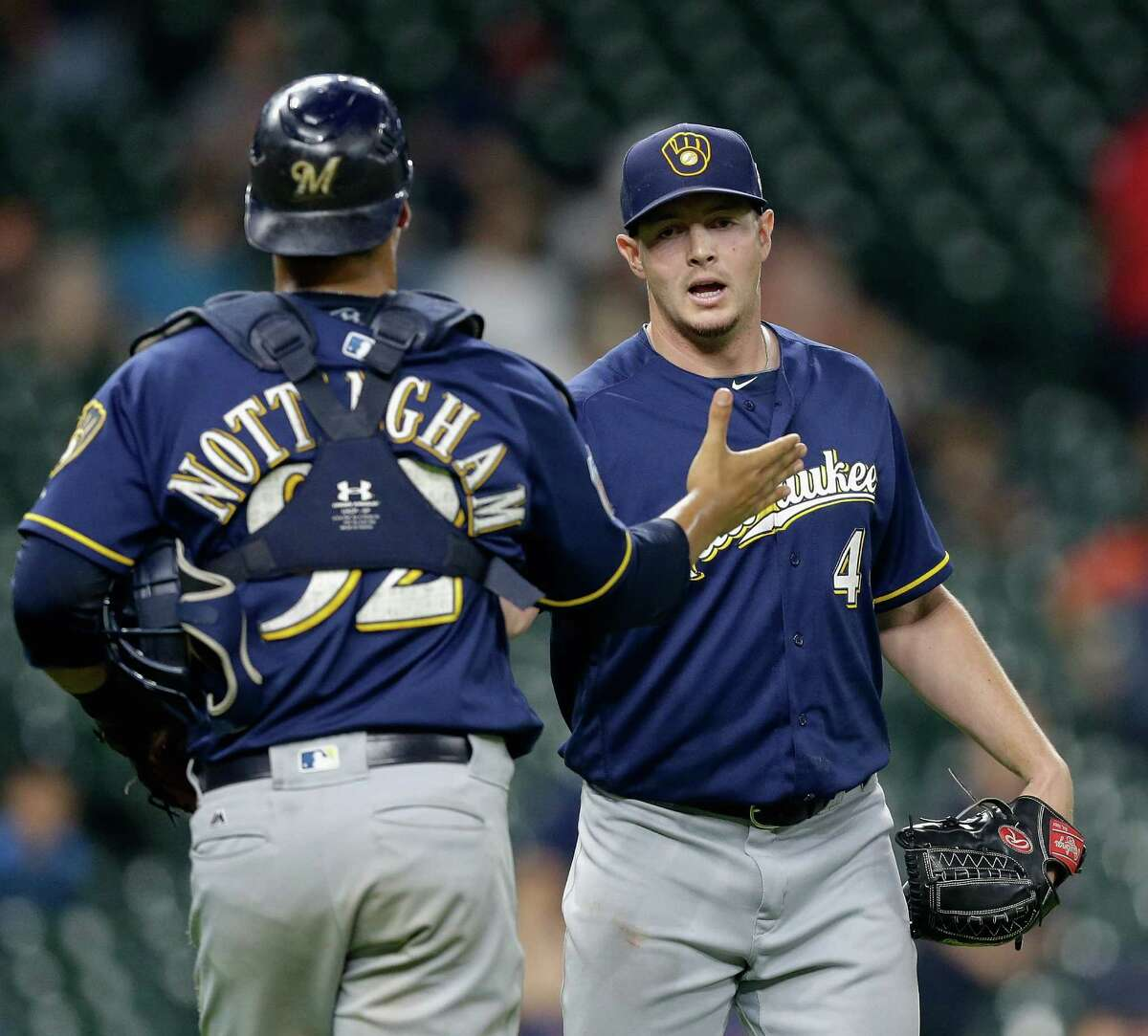 Milwaukee Brewers' Corey Knebel (46) shakes hands with catcher Jacob Nottingham (92) after the final out against the Houston Astros during a spring training baseball game Thursday, March 31, 2016, in Houston. Milwaukee won 6-1.