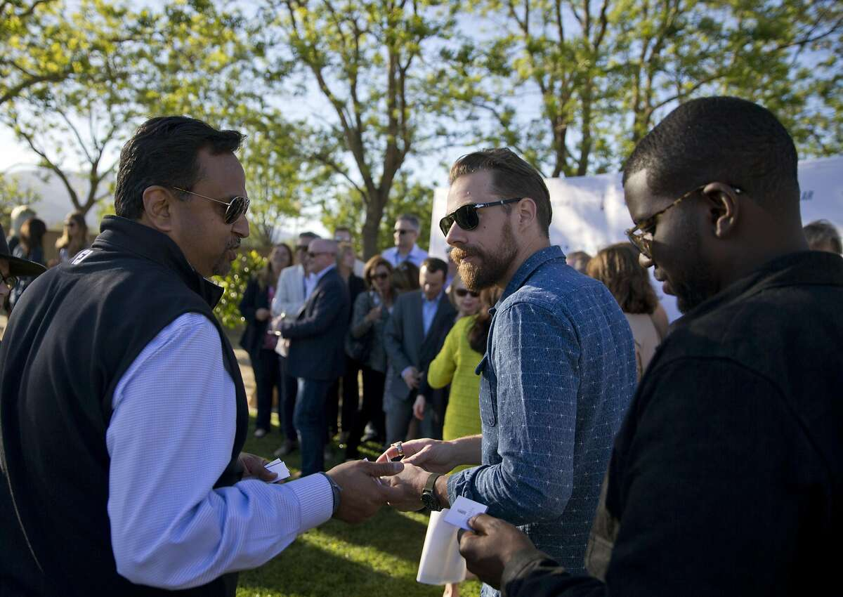 Agnelo Fernandes, left, hands a card to Plain White T's bandmembers Tim Lopez, center, and De'Mar Hamilton, right, at the Yountville Live event in Yountville, Calif., on Thursday, March 31, 2016. Now in its second year, Yountville Live pairs national touring acts, such as the Goo Goo Dolls and Plain White T?s, with celeb wine country chefs and vinters, creating an only-in-Northern-California festival experience that aims to be more low-key and suited to the exclusive nature of the region than BottleRock.
