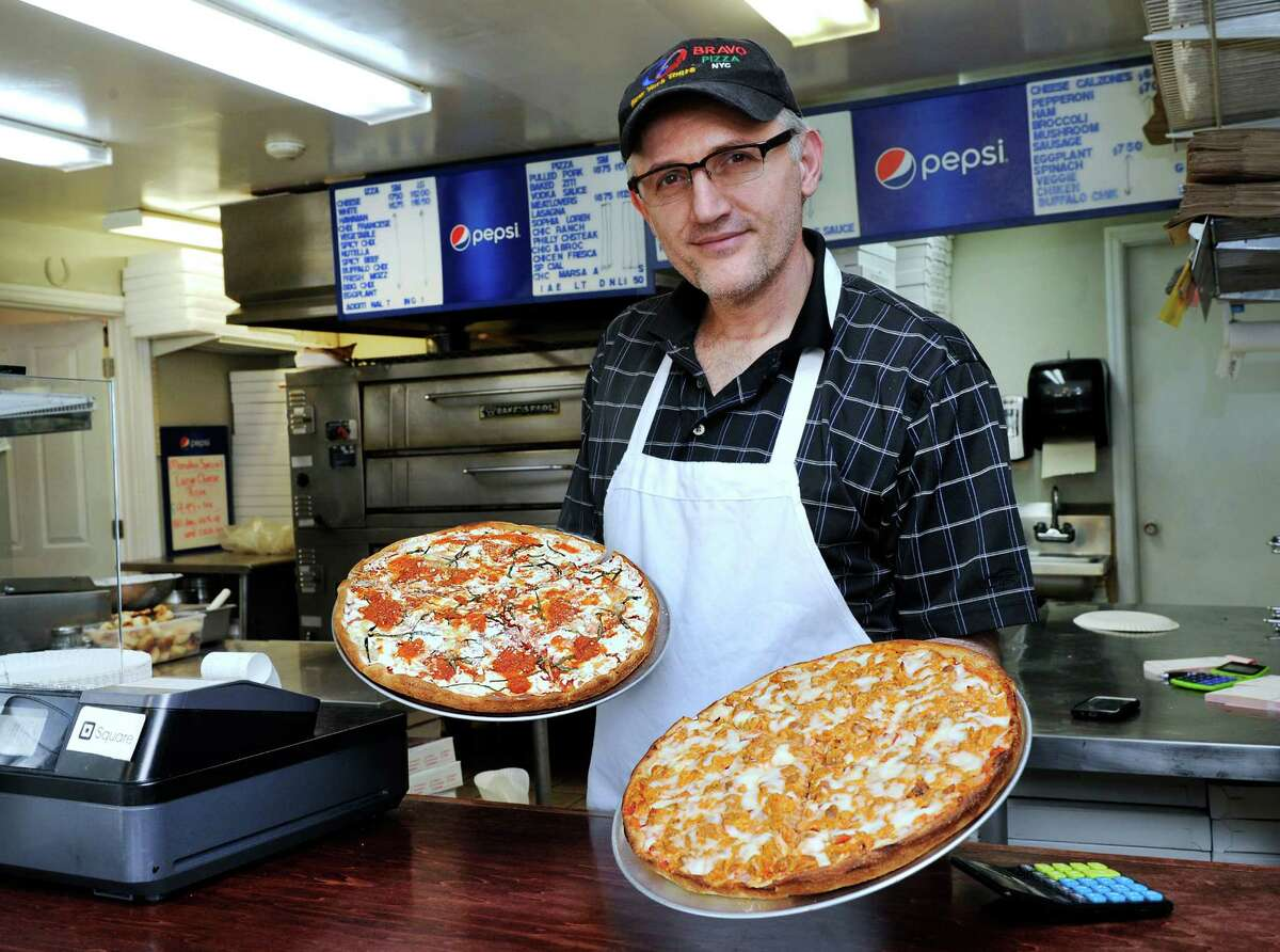 Blear Toci, owner of Bravo NY Pizza on Federal Road in New Milford, holds a fresh mozzarella with basil and marinara pizza on the left, and a buffalo chicken pizza on the right.