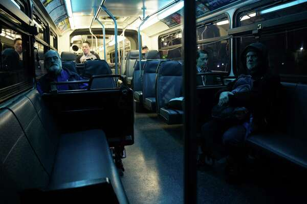 Quiet commuters ride the 27, 33 King County Metro bus route Friday morning, April 1, 2016.
