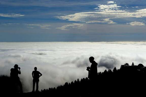 Jessica O'Brien, (left) from Seattle , Brenda Fromolz ,  from Wisconsin and Lenny Cavaluzzi from Walnut Creek enjoy the view of a hugh fog bank rolling into San Francisco Bay while atop Mt. Tamalpais in Marin County on Tuesday Feb. 11, 2014.