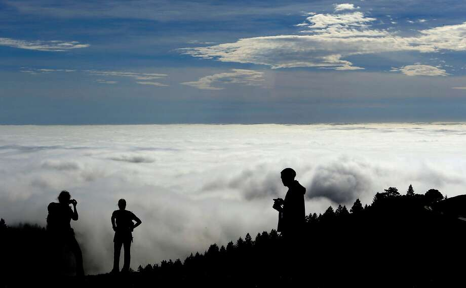 Jessica O'Brien, (left) from Seattle, Brenda Fromolz ,  from Wisconsin and Lenny Cavaluzzi from Walnut Creek enjoy the view of a huge fog bank rolling into San Francisco Bay while atop Mt. Tamalpais in Marin County on Tuesday Feb. 11, 2014. Photo: Michael Macor, The Chronicle