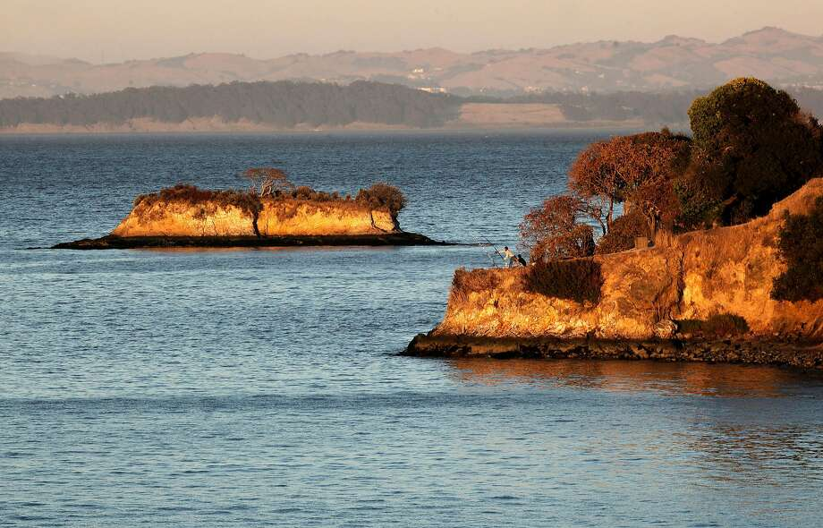 Man fishes off of Five Pines Point with Rat Rock Island in the background at China Camp State Park in San Rafael. Hike to the top of McNears Fire Trail and see five Bay Area bridges. Photo: Michael Macor, The Chronicle