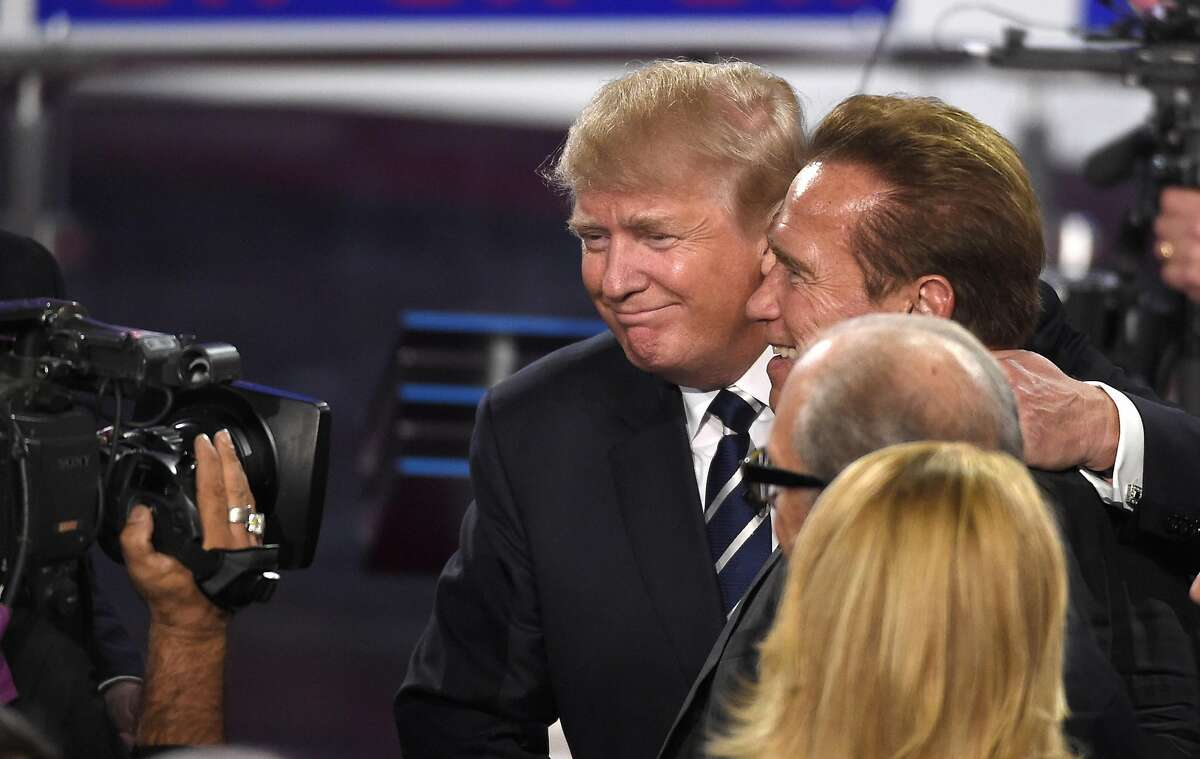 Republican presidential candidate, businessman Donald Trump, center, hugs former California Gov. Arnold Schwarzenegger following the CNN Republican presidential debate at the Ronald Reagan Presidential Library and Museum on Wednesday, Sept. 16, 2015, in Simi Valley, Calif. (AP Photo/Mark J. Terrill)