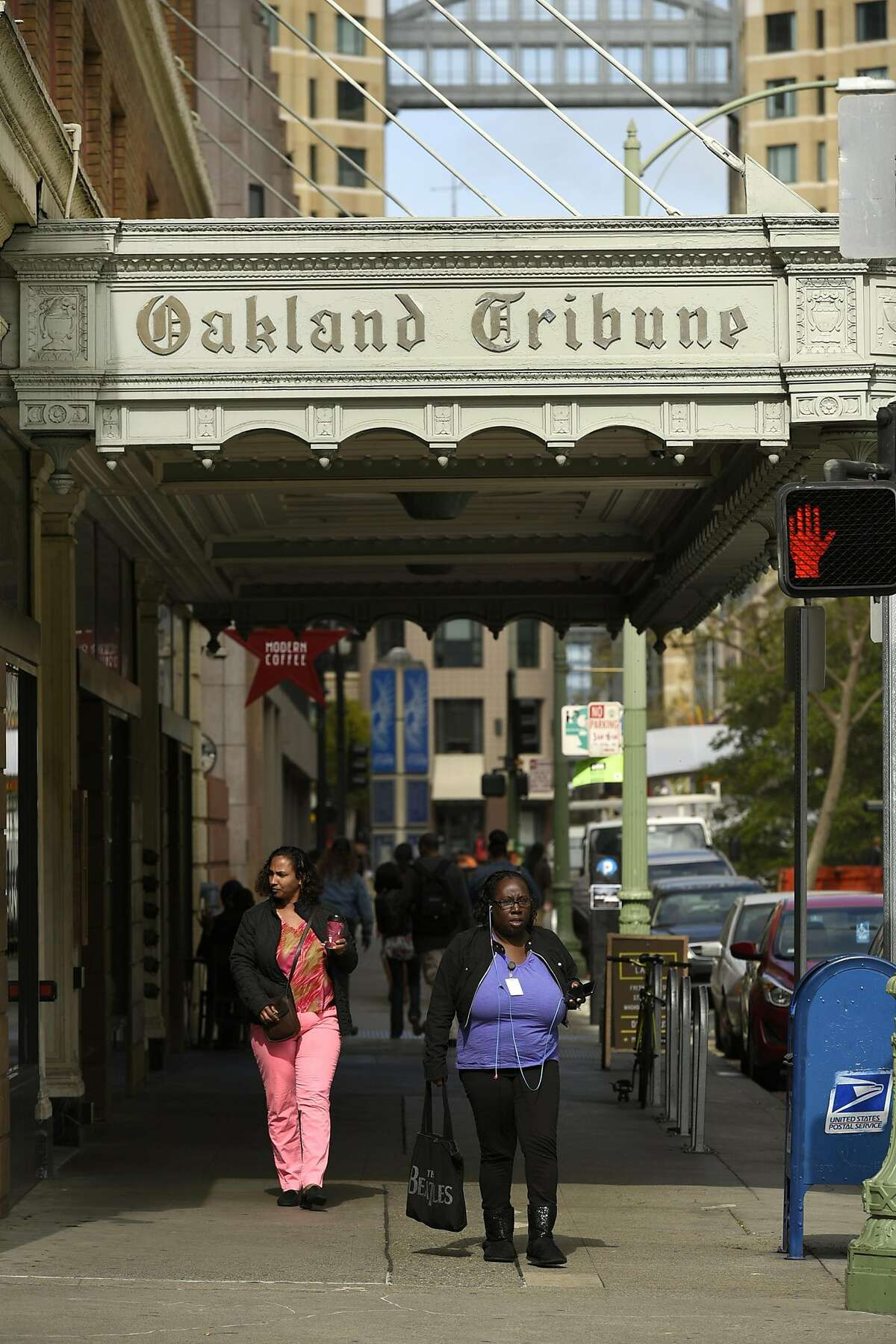 People walk under the marquee of the old Oakland Tribune Tower in Oakland, CA Friday, April 1, 2015.