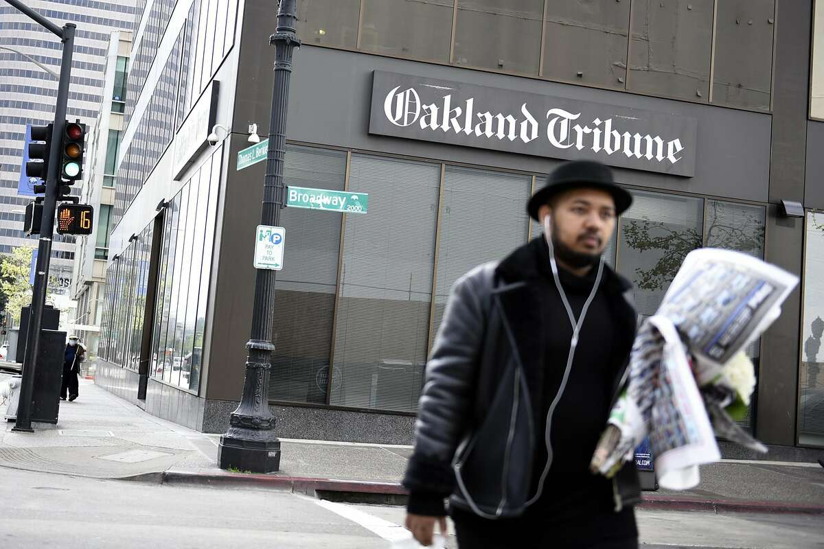 A pedestrian walks past the Oakland Tribune's current offices on Broadway in Oakland, CA Friday, April 1, 2015.