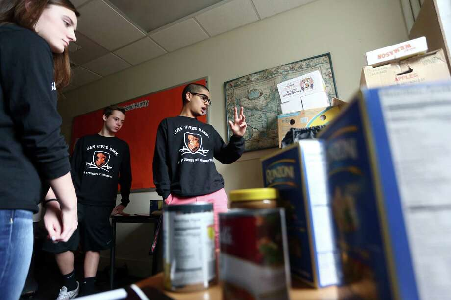 SHS Gives Back co-president Nick Rao, 16, discusses the process of finding students, keeping them anonymous and giving them a bag of essential food products while inside a Stamford High School room used as a food pantry. Photo: Michael Cummo / Hearst Connecticut Media / Stamford Advocate
