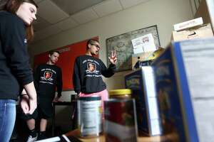 SHS Gives Back co-president Nick Rao, 16, discusses the process of finding students, keeping them anonymous and giving them a bag of essential food products while inside a Stamford High School room used as a food pantry.