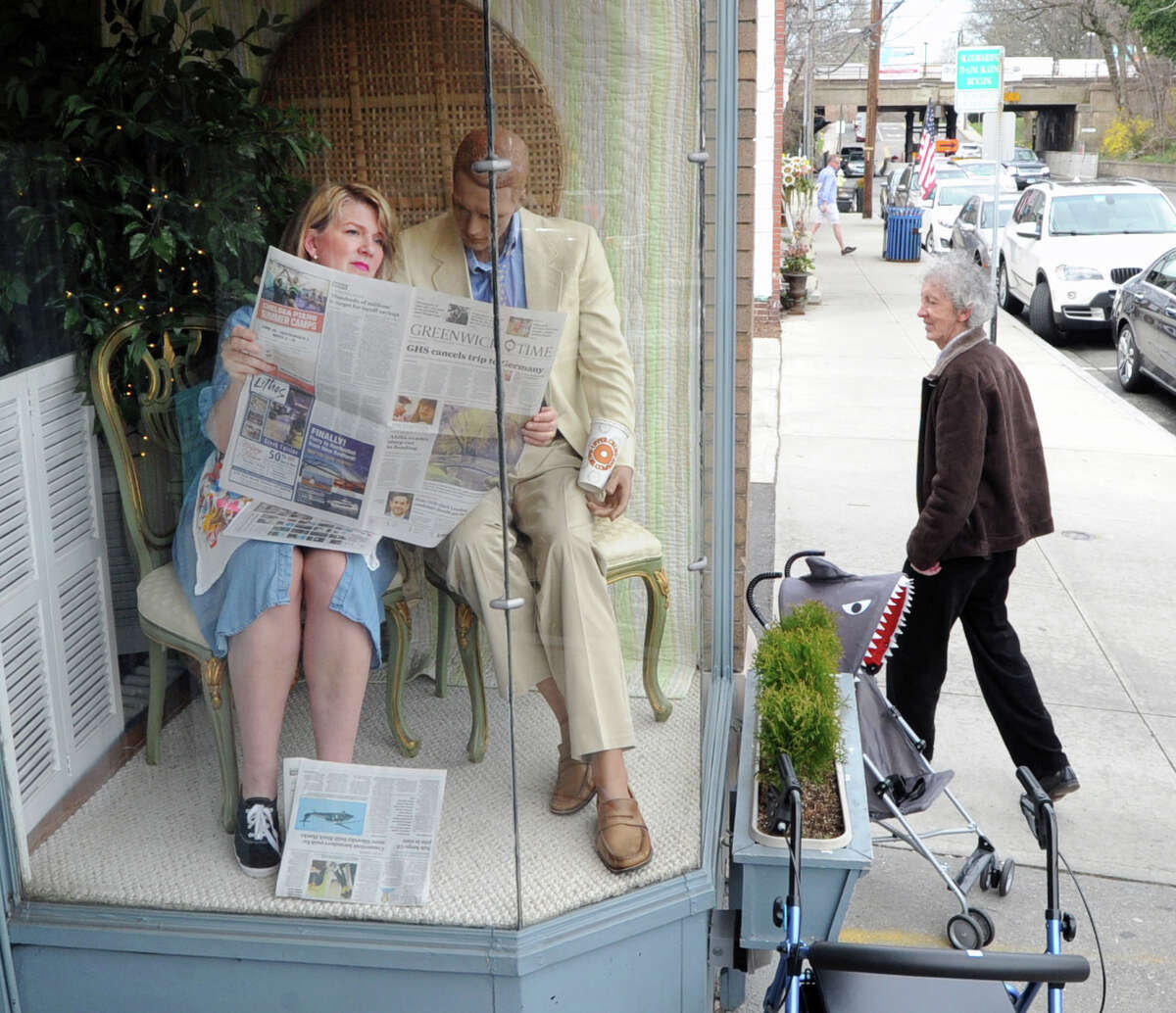 Liz Gustavson, left, reads a copy of the Greenwich Time as she plays a mannequin as part of the traditional April Fool's Day prank at the Rummage Room on Sound Beach Avenue in Old Greenwich, Conn., Friday, April 1, 2016. The Rummage Room, is a second-hand shop that is operated to raise money for various causes by the Women's Fellowship of the First Congregational Church in Old Greenwich of which Gustavson is a member. Gustavson said about the April Fool's Day prank