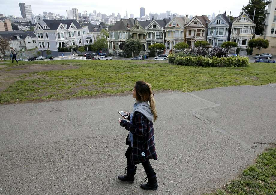 Top: Diana Hoang takes a tour of the Western Addition neighborhood past the Painted Ladies on Alamo Square using the Detour application in San Francisco. Photo: Connor Radnovich, The Chronicle
