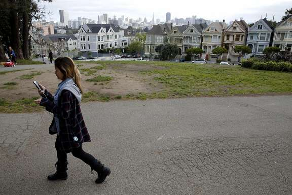 Diana Hoang takes a tour of the Western Addition neighborhood near the Painted Ladies using the Detour application in San Francisco, California, on Wednesday, March 31, 2016.