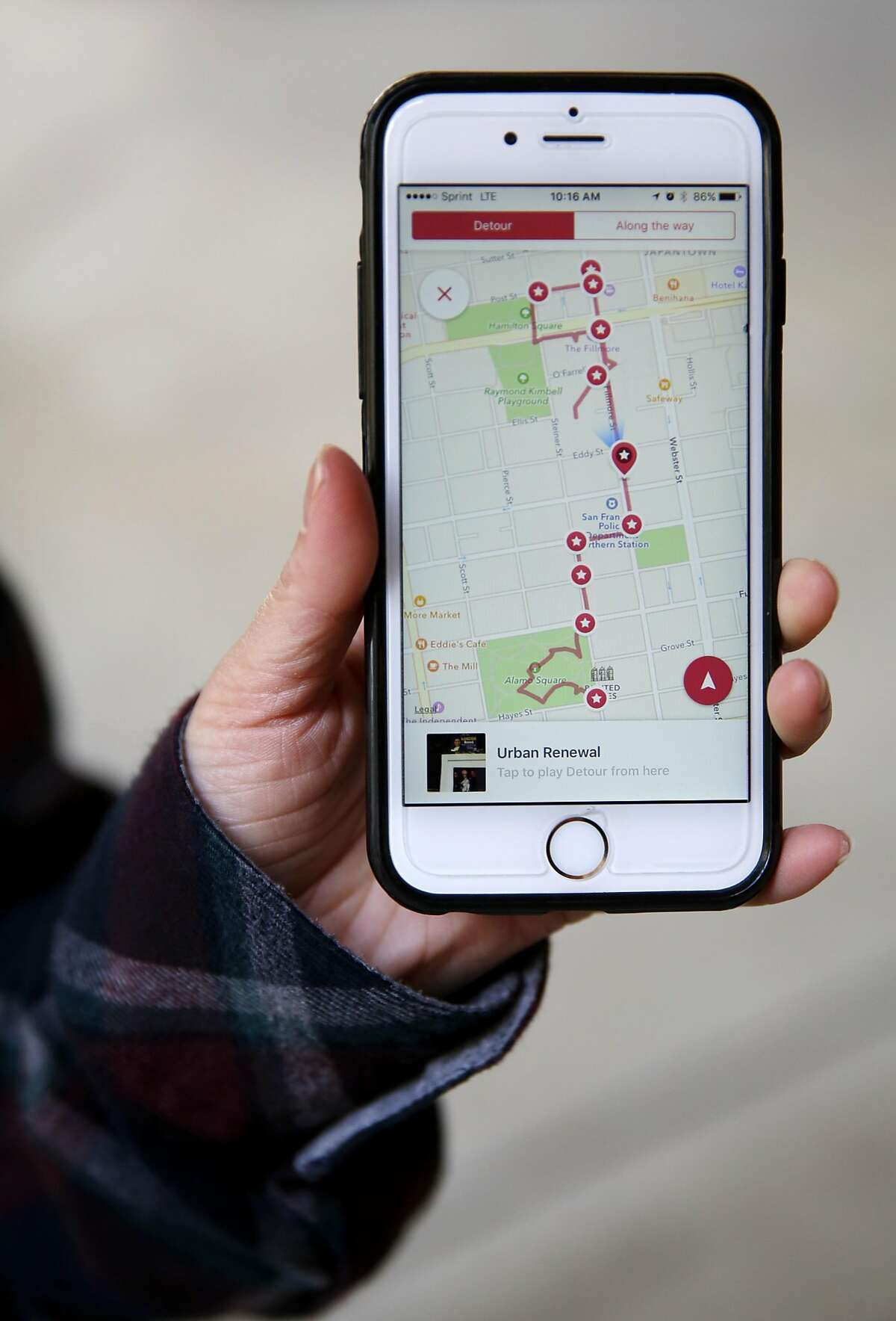 Diana Hoang shows the Detour application while on a tour of the Western Addition neighborhood in San Francisco, California, on Wednesday, March 31, 2016.