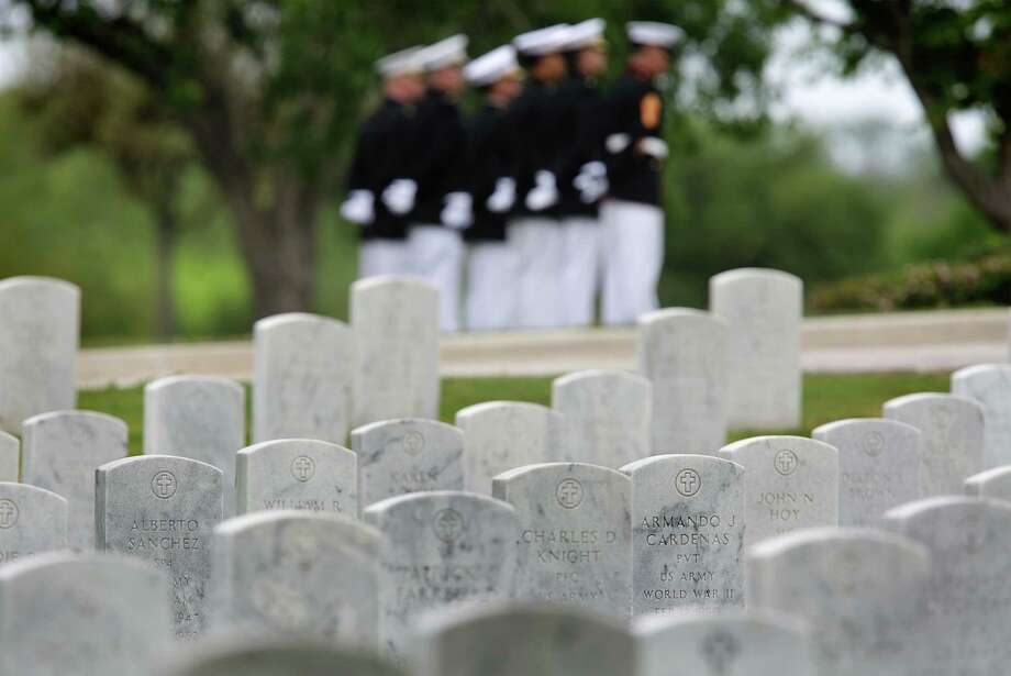 Marines attending the April 1 burial service of Army Sgt. Santiago Erevia, a Medal  of Honor recipient, are seen  in the background at Fort Sam National Cemetery. Photo: Bob Owen / San Antonio Express-News / San Antonio Express-News