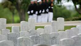 Marines attending the April 1 burial service of Army Sgt. Santiago Erevia, a Medal  of Honor recipient, are seen  in the background at Fort Sam National Cemetery.