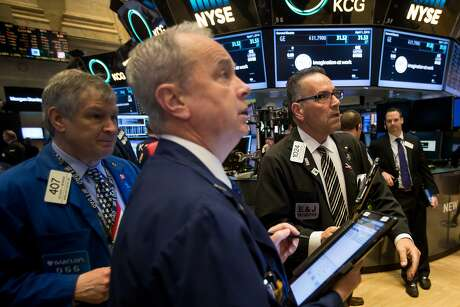 Traders work on the floor of the New York Stock Exchange (NYSE) in New York, U.S., on Friday, April 1, 2016. U.S. stock-index futures fell, tracking declines in crude oil, amid data showing job gains and higher wages that supported the case for raising interest rates. Photographer: Michael Nagle/Bloomberg