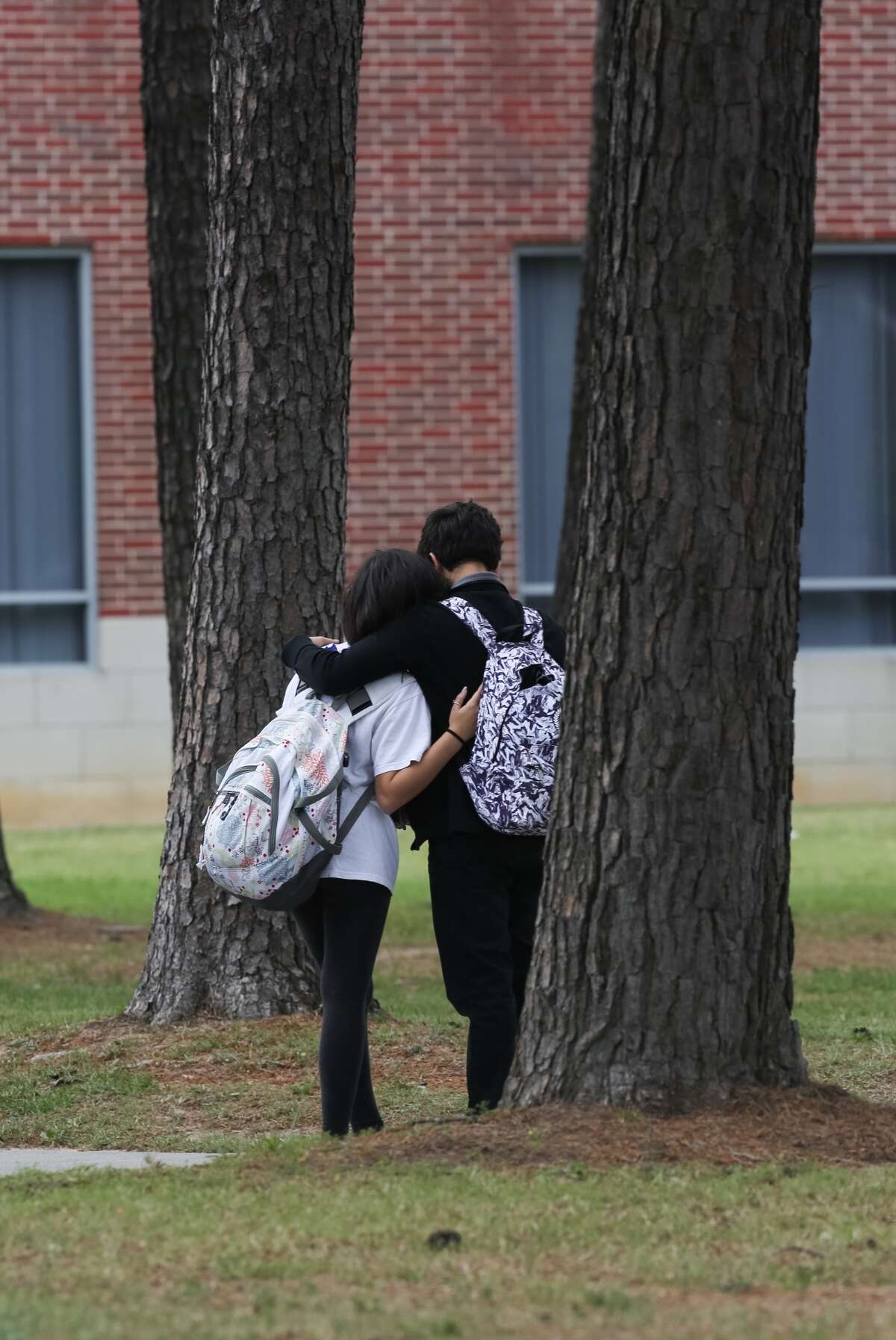 Two students embrace after classes let out at Klein Collins High School, Friday, April 1, in Spring. A 9th grade student fell from a second-story balcony around 12:40 p.m. and was transported by Life Flight to Memorial Hermann Hospital. ( Jon Shapley / Houston Chronicle )