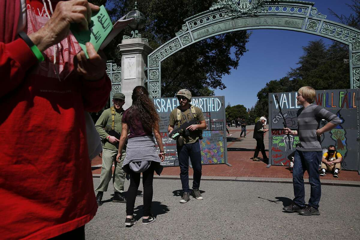 David McCleary, right, takes video as protesters who preferred not to give their names role play as Israeli soldiers with people role playing Palestinians during a mock Israeli check-point demonstration near the Sather Gate on the University of California, Berkeley campus March 29, 2016 in Berkeley, Calif. The event was sponsored by Students for Justice in Palestine and was part of a week of events meant to raise awareness about the Palestinian situation.