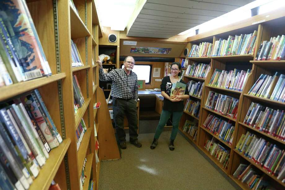 Ferguson Library employees Wyc Bentley, left, and Ashley Hamel pose inside the Bookmobile during a stop at the Chester Addison Community Center. The Bookmobile, Ferguson Library's converted bus, has books, DVD's and audiobooks available to anyone with a library card and makes stops across the city every weekday. Photo: Michael Cummo / Hearst Connecticut Media / Stamford Advocate