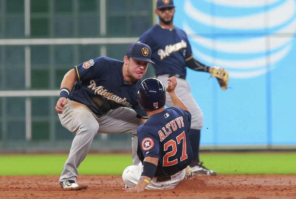 Houston Astros' Jose Altuve is caught stealing by Milwaukee Brewers second baseman Scooter Gennett during the third inning of an exhibition baseball game, Friday, April 1, 2016, in Houston.
