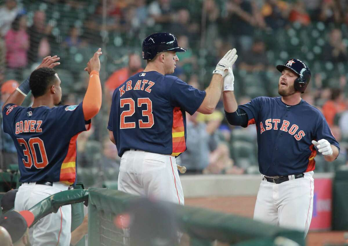 Houston Astros' Tyler White is greeted by teammates Erik Kratz and Carlos Gomez after his solo home run against the Milwaukee Brewers in the second inning of an exhibition baseball game Friday, April 1, 2016 in Houston.