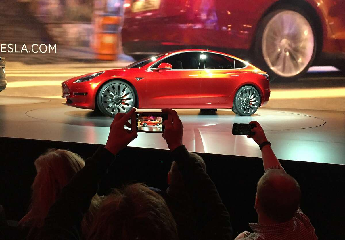 Tesla Motors unveils the new lower-priced Model 3 sedan at the Tesla Motors design studio in Hawthorne, Calif., Thursday, March 31, 2016. It doesn't go on sale until late 2017, but in the first 24 hours that order banks were open, Tesla said it had more than 115,000 reservations. Long lines at Tesla stores, reminiscent of the crowds at Apple stores for early models of the iPhone, were reported from Hong Kong to Austin, Texas, to Washington, D.C. Buyers put down a $1,000 deposit to reserve the car. (AP Photo/Justin Prichard)