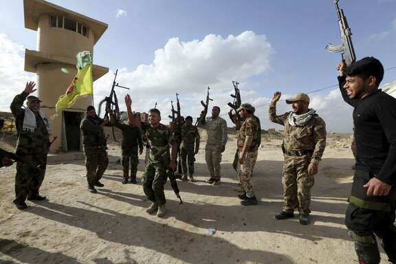 Shiite fighters chant slogans Feb. 7 against the Islamic State at the frontline in Tikrit, Iraq, 80 miles north of Baghdad. Iraqs Shiite militias, mobilized in 2014 to fight the Islamic State group, are now showing they have no intention to stand down once the fight against the Sunni extremists is over.