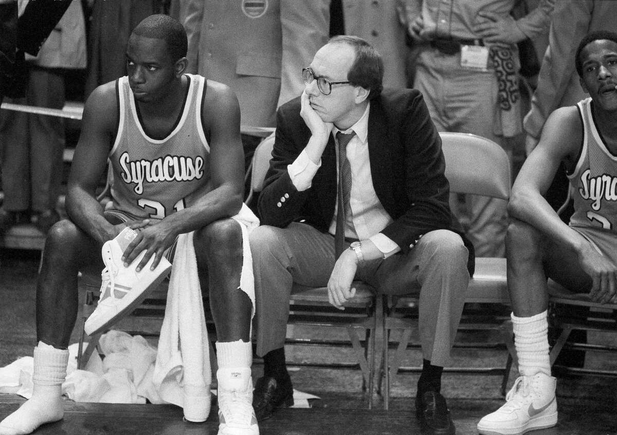FILE - In this March 10, 1984, file photo, Syracuse coach Jim Boeheim, right, and Syracuse player Dwayne Washington (31) watch as Georgetown University took control in overtime of the Big East Conference championship basketball game at Madison Square Garden in New York. Syracuse coach Jim Boeheim, current and former players, and others associated with the program continue to rally in support of former Orange star Dwayne Pearl Washington, who's afflicted with brain cancer.