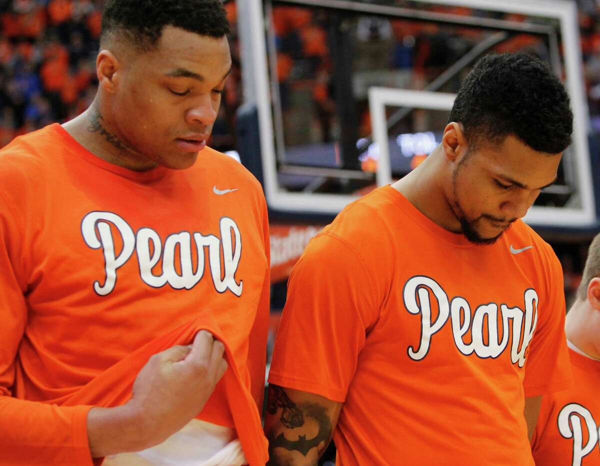 FILE - In this Jan. 30, 2016, file photo, Syracuse's Dajuan Coleman, left, and Michael Gbinije, right, wear shirts in support of Syracuse basketball great Dwayne