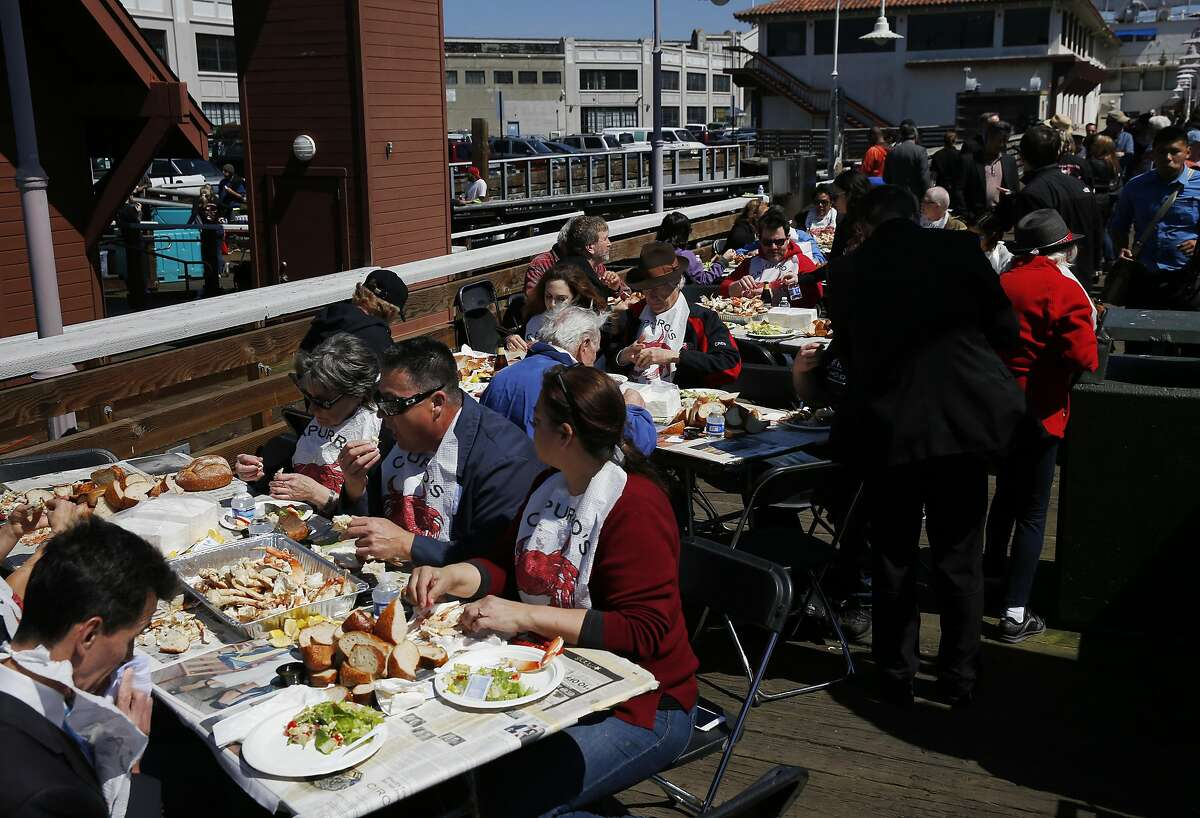 People eat fresh dungeness crab during a crab feed near Pier 45 on the Fisherman's Wharf April 1, 2016 in San Francisco, Calif.