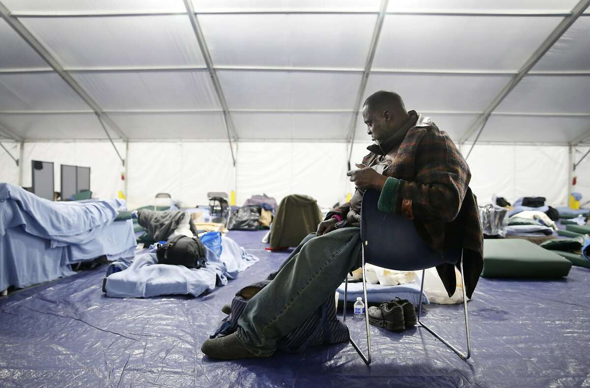 Melvin King organizes his belongings next to his bed at the homeless shelter on Pier 80 in San Francisco, Calif. on Friday, April 1, 2016.