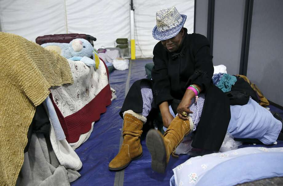 A homeless woman prepares to head out for the day at the shelter on Pier 80, which is close to capacity each night. Photo: Paul Chinn, The Chronicle