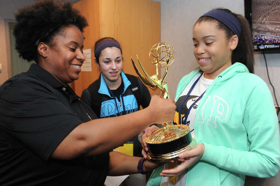 Denisha McPherson, left, an engineer with NBC Sports in Stamford, hands one the Emmy Awards her group has won to Ayanna Wilson, right, a junior at Fairchild Wheeler Multi-Magnet School, during the Bridgeport Youth Summit at the Webster Bank Arena on Friday. Wilson is with her classmate, Julia Antones, center. Photo: Ned Gerard / Hearst Connecticut Media / Connecticut Post