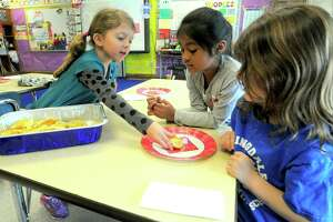Violet Mohr,a student in Laura Cruz kindergarten class at Springdale School in Stamford, passes out Pastelito's, a Cuban treat to her classmates on April 1, 2016. Mohr's grandmother immigrated from Cuba in 1961. The class was celebrating her culture as part of a year-long celebration of diversity.