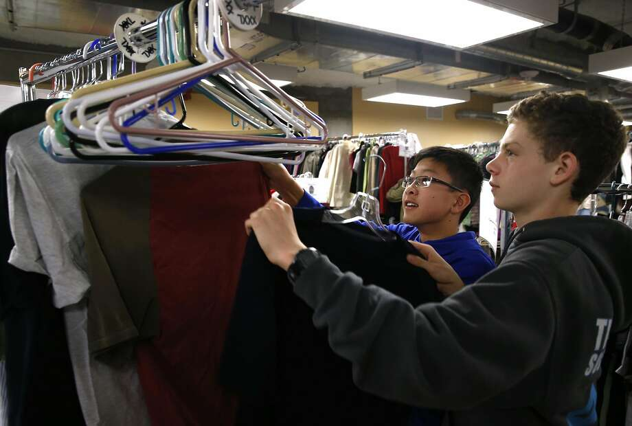 Volunteers Andrew Chang (left) and Ethan Ostrow, students at San Francisco Friends School, organize donated clothing at St. Anthony Dining Room. Photo: Paul Chinn, The Chronicle