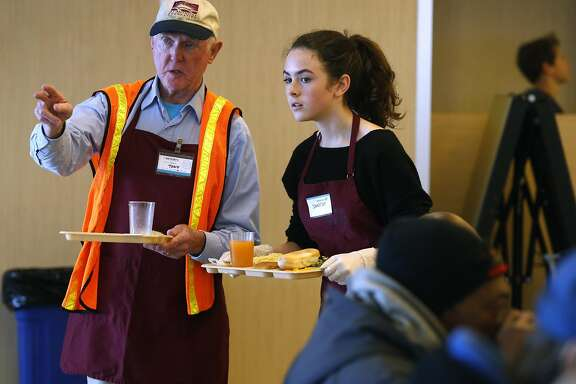 Somerset Miles-Dwyer (right), a student from the San Francisco Friends School, receives direction from Tony Hanley at the St. Anthony's Dining Room in San Francisco, Calif. on Friday, April 1, 2016.