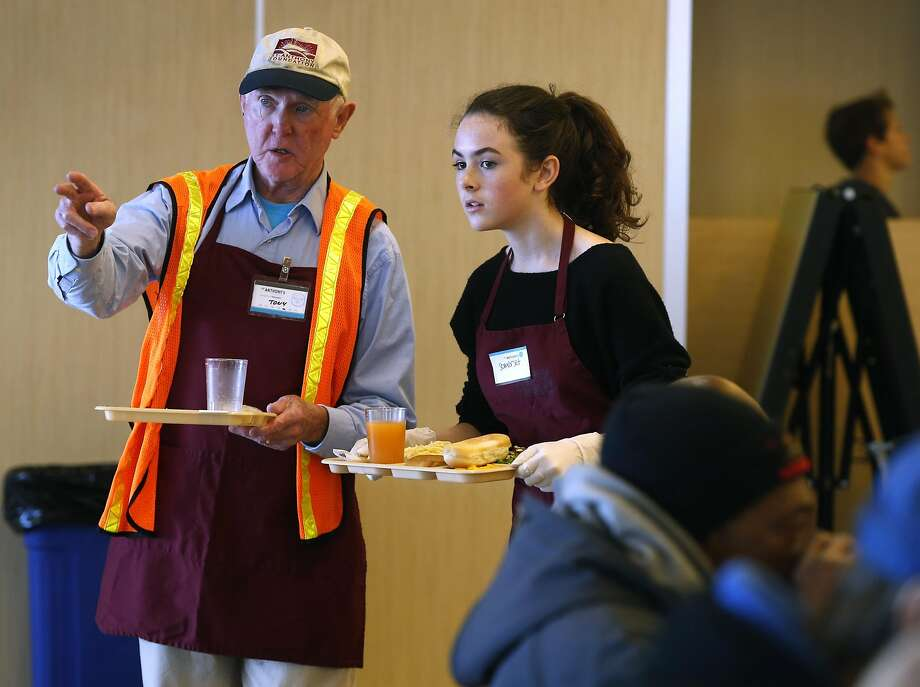 Tony Hanley guides San Francisco Friends School student Somerset Miles-Dwyer while she volunteers at St. Anthony Dining Room. Photo: Paul Chinn, The Chronicle