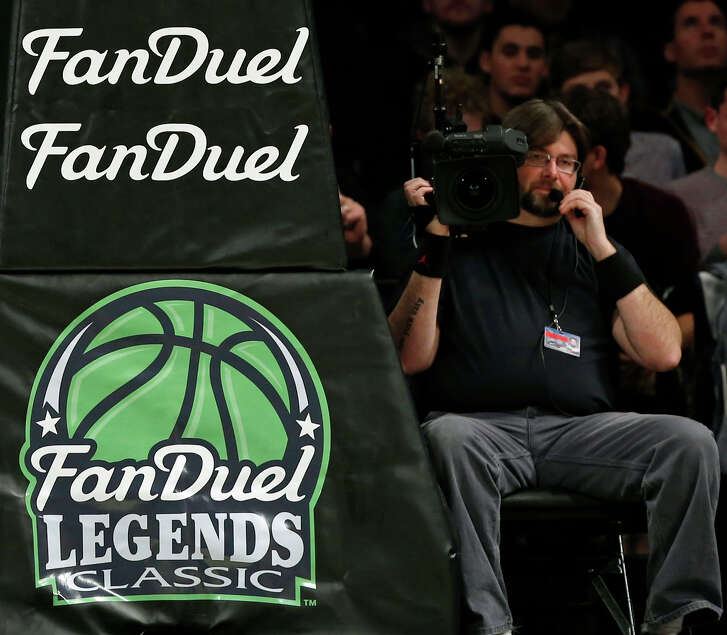 FILE - In this Nov. 24, 2015 file photo, FanDuel advertising covers the post at an NCAA college basketball matchup in the FanDuel Legends Classic consolation game, at the Barclays Center in New York. Daily fantasy sports companies have said their industry remains viable despite a rocky start to 2016. FanDuel confirmed it was laying off 55 workers in its Orlando, Fla., office, and ESPN and DraftKings ended an exclusive advertising deal.  (AP Photo/Kathy Willens, File)