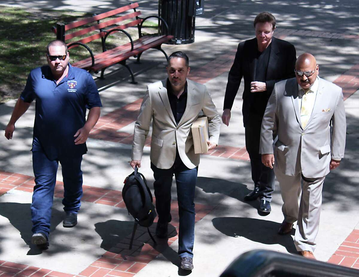 Stephen Moody (from the left), Greg Brockhouse, Stanley Bernstein and Rudy Morales deliver signatures to City Hall on Thursday. They say more than 6,000 have signed petition opposing San Antonio Water System rate hikes.