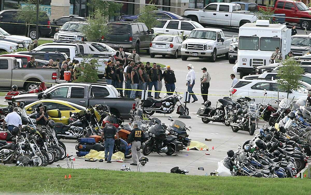 FILE - In this May 17, 2015 file photo, authorities investigate a shooting in the parking lot of the Twin Peaks restaurant, in Waco, Texas.Four of the nine people killed in a melee between rival biker gangs outside a Texas restaurant were struck by the same caliber of rifle fired by Waco police, according to evidence obtained by The Associated Press that provides the most insight yet into whether authorities were responsible for any of the deaths and injuries. (AP Photo/Jerry Larson, File)