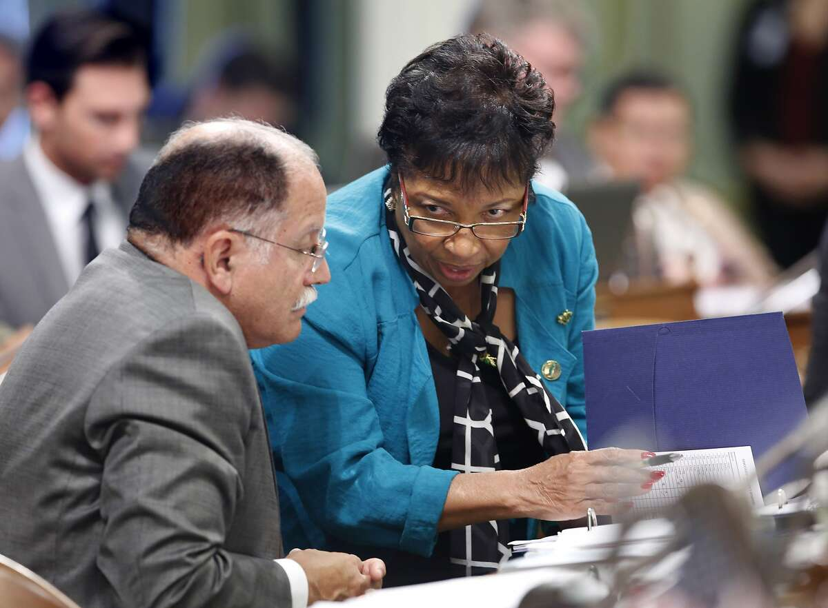 FILE - In this Sept. 10, 2015 file photo Assemblywoman Cheryl Brown, D-San Bernardino, talks with Assemblyman Jose Medina, D-Riverside, during the Assembly session in Sacramento, Calif. Brown faces an unexpected challenge from the left this year as political fallout for her moderate votes. Environmentalists, labor organizations and advocates of stricter gun laws are teaming up to try to unseat her. (AP Photo/Rich Pedroncelli, File)