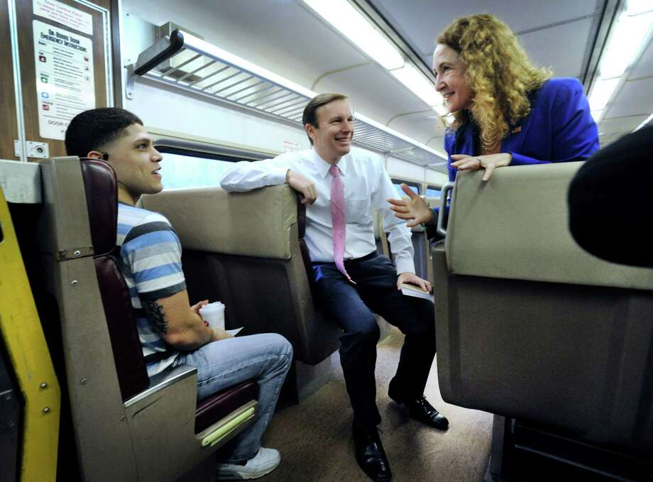 Ben Guzman, 25, left, of Danbury, chats with U.S. Sen. Chris Murphy and U.S. Rep. Elizabeth Esty  on a Metro-North train  to Norwalk Friday. Photo: Carol Kaliff / Hearst Connecticut Media / The News-Times