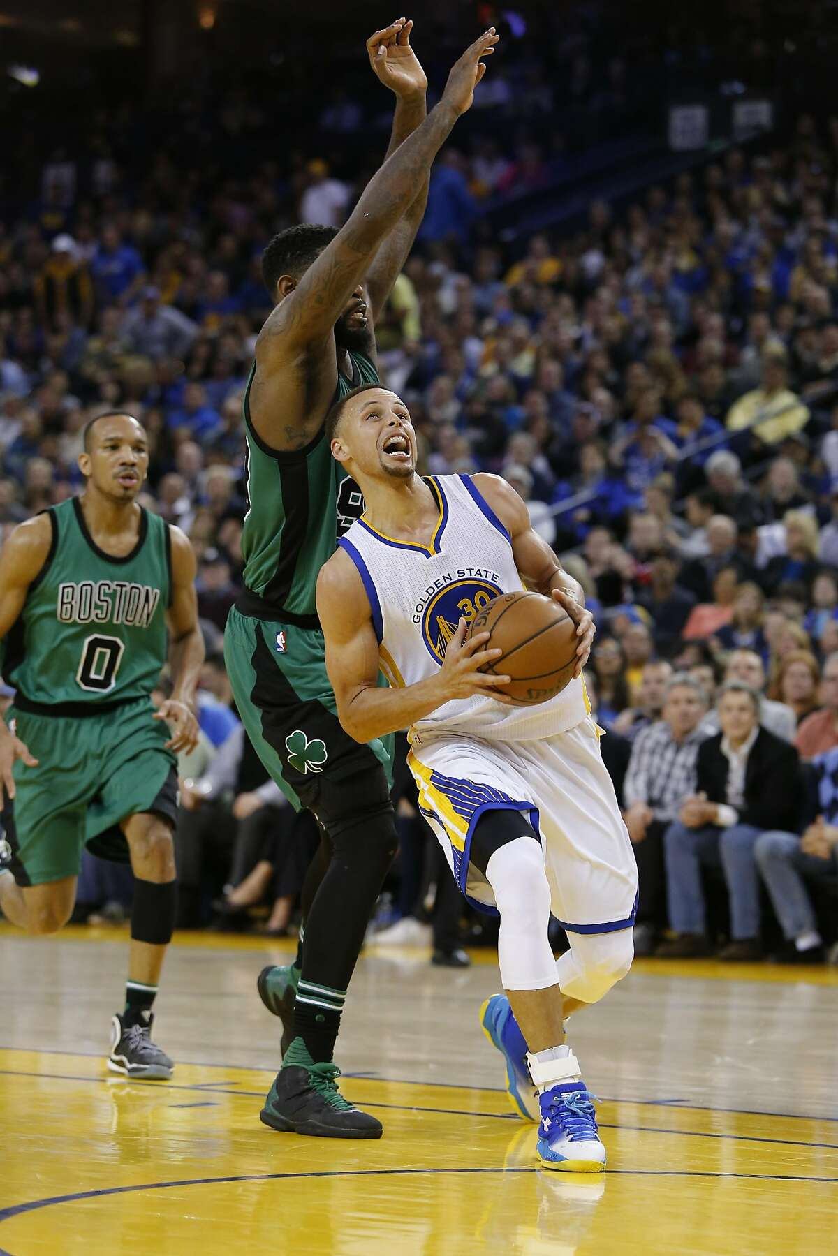 Warriors' Stephen Curry, 30 drives past the Celtics' Amir Johnson, 90 in the second half, as the Golden State Warriors went on to lose to the Boston Celtics 106-109 in NBA action at Oracle Arena, in Oakland, California, on Fri. April 1, 2016