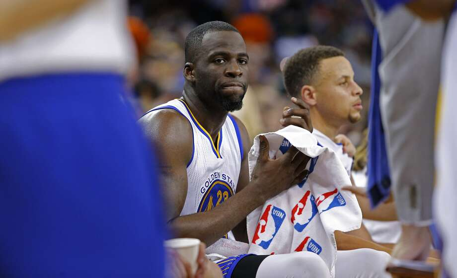 Draymond Green (left) and Stephen Curry sit during a timeout in the fourth quarter Friday, in which the Warriors never led the Celtics. Photo: Michael Macor, The Chronicle