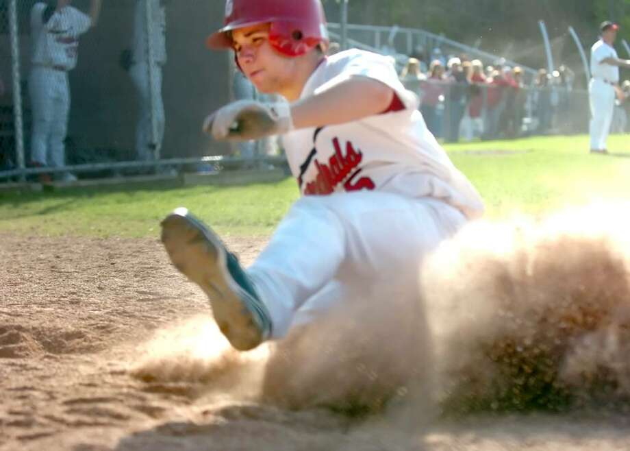 Greenwich High School's Joey Marianacci (#5) slides into home base in the baseball ball game against West Hill High School hosted by Greenwich on Monday, April 12, 2010.  Greenwich won 12-1. Photo: Helen Neafsey / Greenwich Time