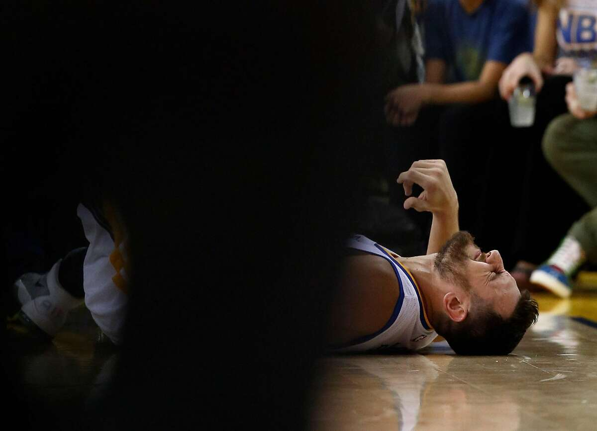 Andrew Bogut of the Golden State Warriors lies on the court after injuring his ribs during their game against the Boston Celtics at ORACLE Arena on April 1, 2016 in Oakland, California.