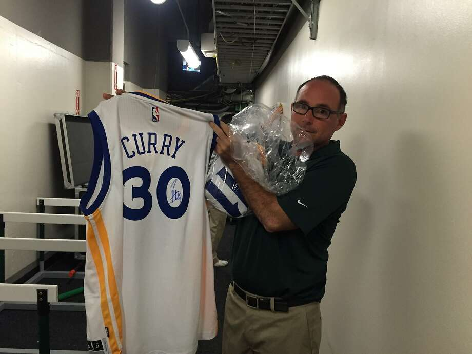 A's visiting clubhouse manager Mike Thalblum displays the signed Stephen Curry jersey awarded to the winner of the team's free-throw contest Saturday. Photo: Susan Slusser/The Chronicle