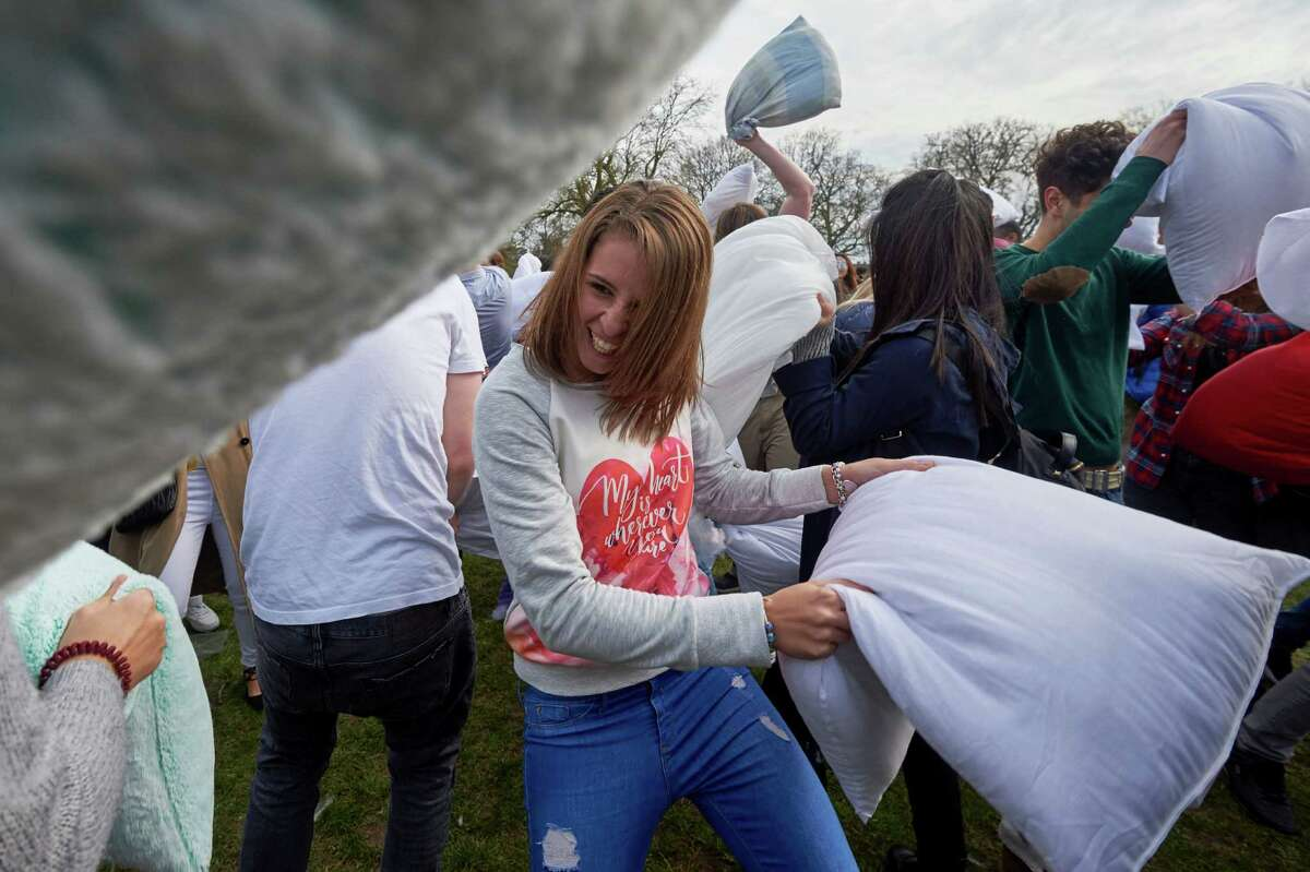 Revellers take part in a mass pillow fight in Kennington Park in south London on International Pillow Fight Day, April 2, 2016. / AFP / Niklas HALLE'N