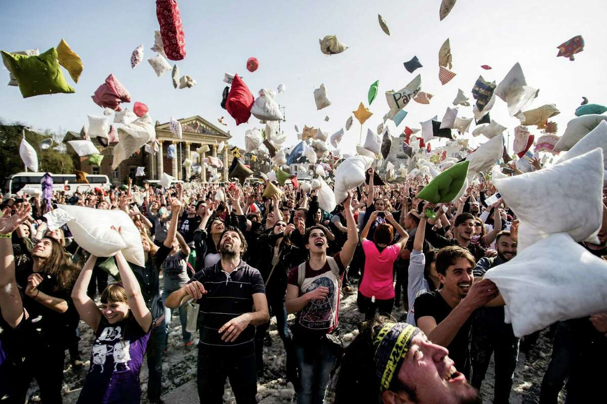Young people throw pillows into the air as they mark International Pillow Fight Day in the Heroes' Square, in central Budapest, Hungary, Saturday, April 2, 2016. (Zoltan Balogh/MTI via AP)